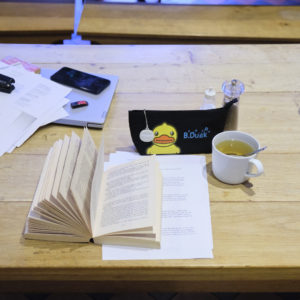 Photo of a desk with an open book, a cup, a pencil case and some papers