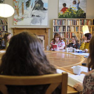Photo of Foyle Young Poets sitting round a circular table with notebooks. Em power reads from her work.