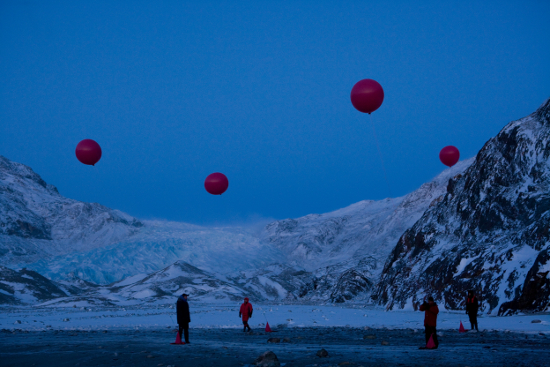A twilight photograph of an artic region, with balloons representing greenhouse gases in the air