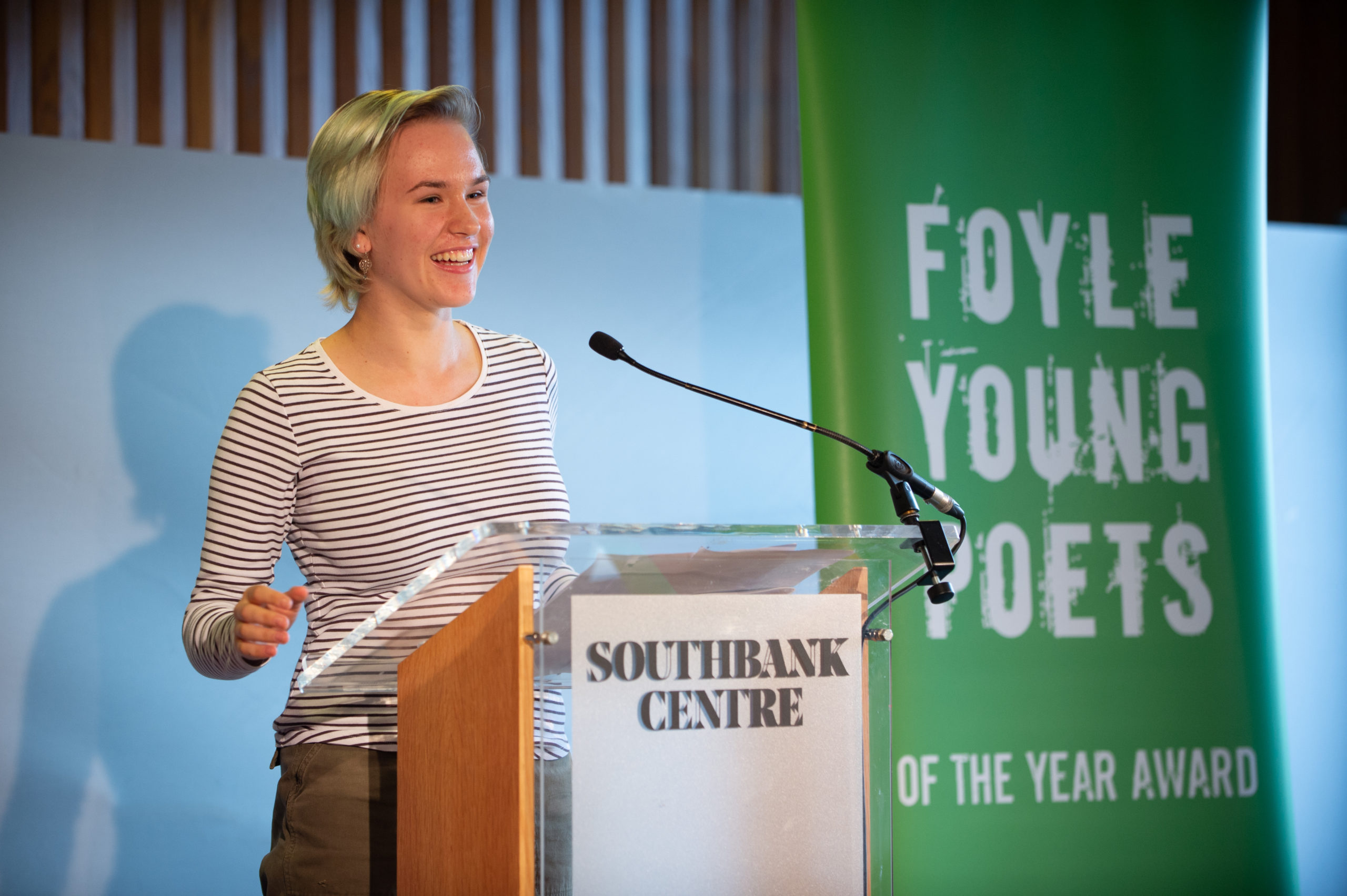 Elizabeth Thatcher smiles reading at a podium next to a green banner that says Foyle Young Poets