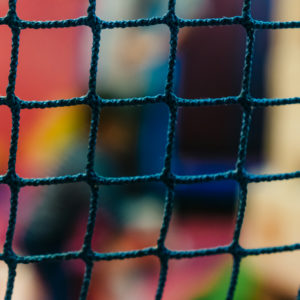 Photo: blue net of rope with multicoloured out of focus background.