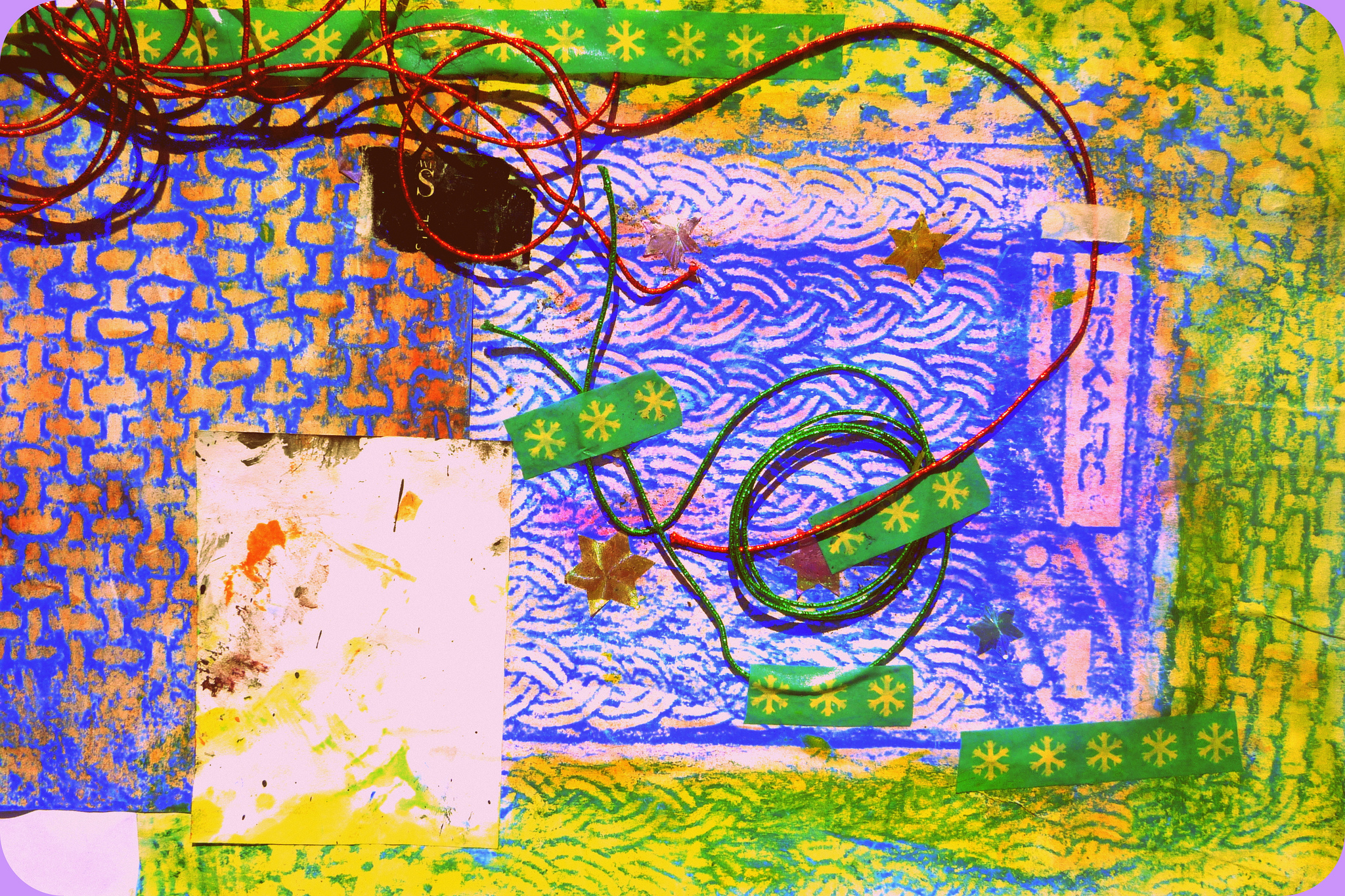 collage including stamps, brightly coloured paper and paints, and wires stuck down with green starry tape
