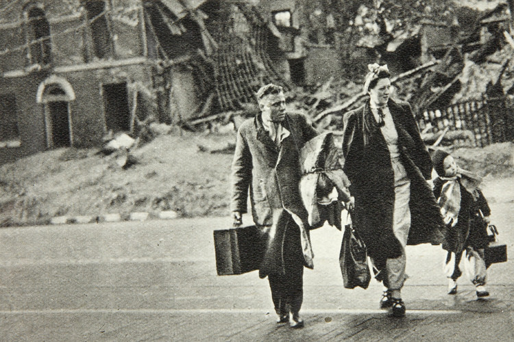 A family cross the road with their possessions following a bombing raid in WWII