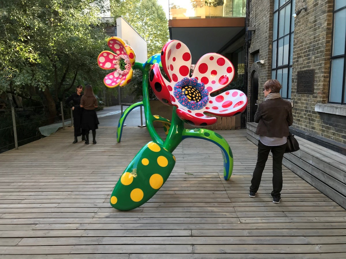 Photo taken outside on some wooden planked flooring. Two people walk past a giant, brightly decorated flower which leans to one side. The stem is green with yellow spots; the flower itself is pink with black spots on the outside and white with pink spots on the inside, with purple pollen in the centre.