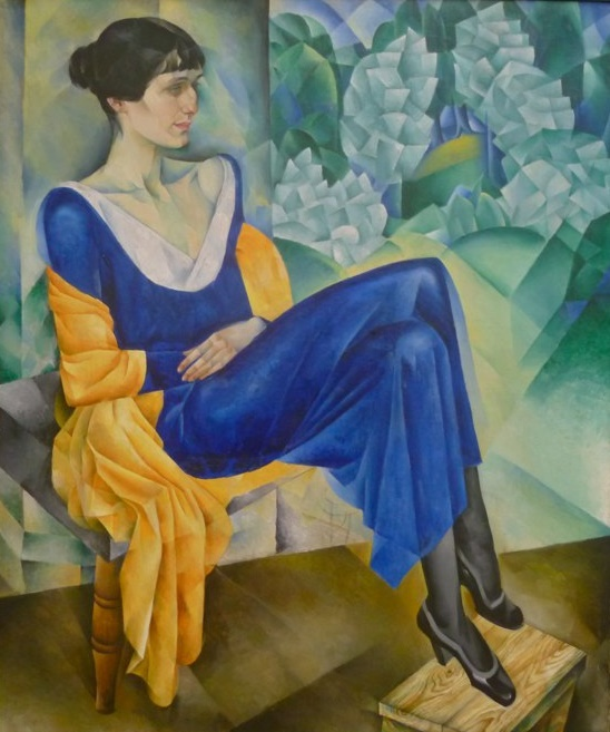Oil painting of Anna Akhmatova, with sharp lines and bold colours - a yellow shawl draped on the chair, her arms and legs crossed in a blue dress