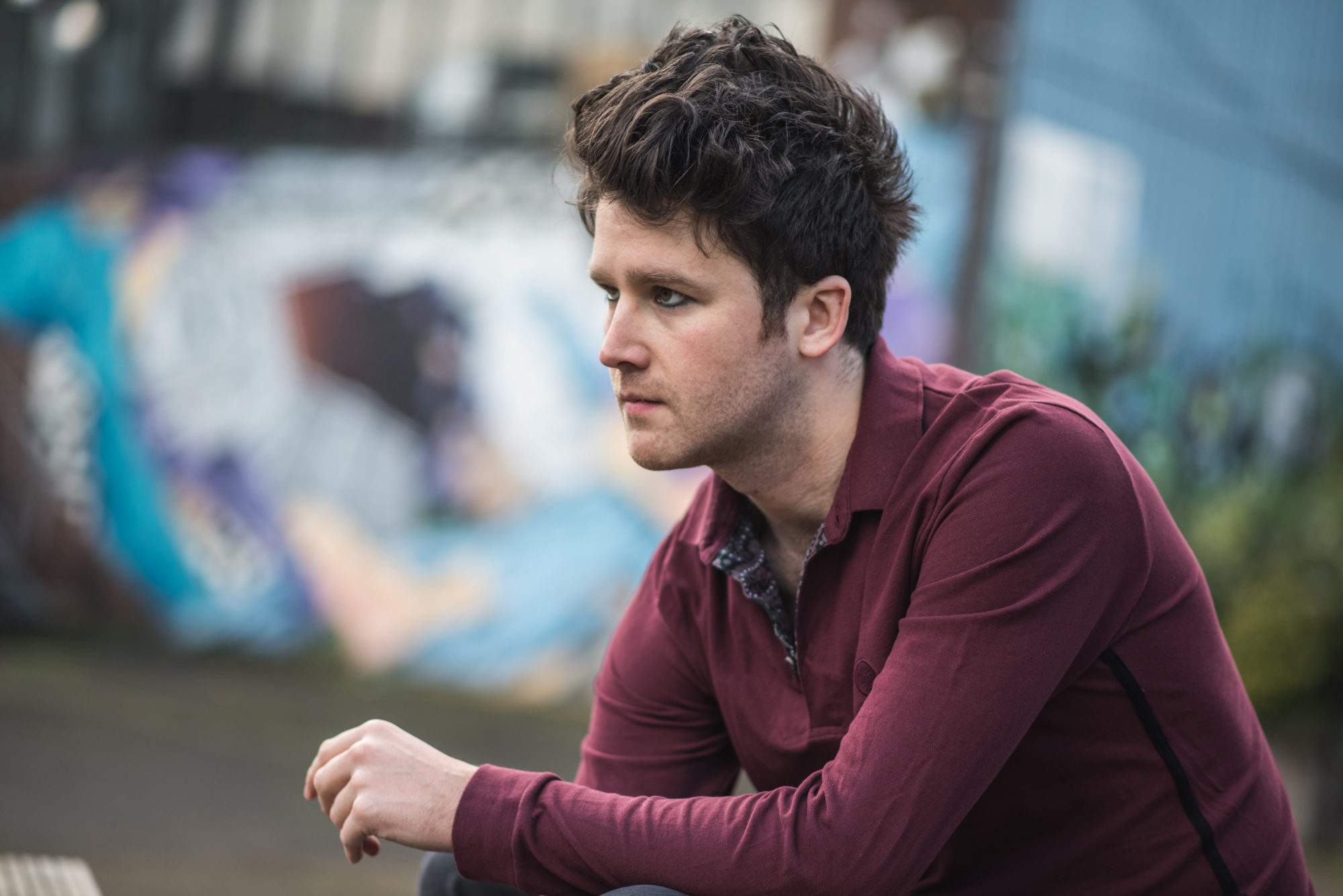Matt, sitting, looks to the side wearing a burgundy jumper