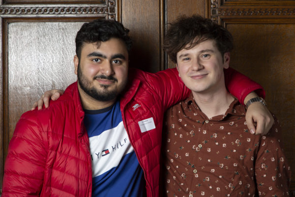 Photo of two young people smiling with their arms round one another
