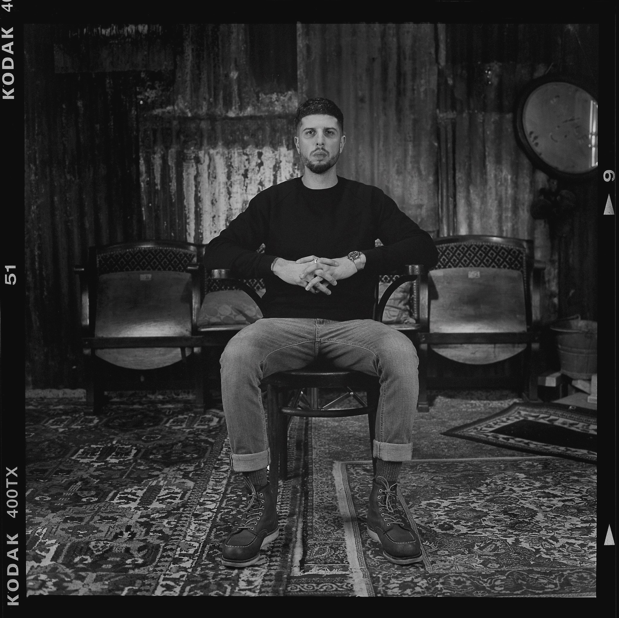 Black and white photo of Anthony Anaxagorou - he sits on a chair in the middle of a room with Persian rugs across the floor. The wall seems to be made of corrugated iron. He sits, legs akimbo and hands clasped, with his elbows on the armrests. He wears a black jumper, jeans and boots.