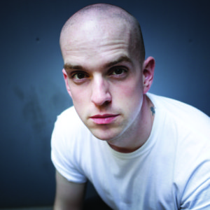 Andrew McMillan leans forward in a white t-shirt. He is white, has a shaven head and is pouting slightly.