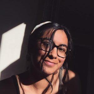 Anisha Minocha, a young Indian woman with big black glasses, smiling