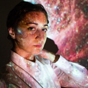 Photo of Astra with pink galaxies projected onto her