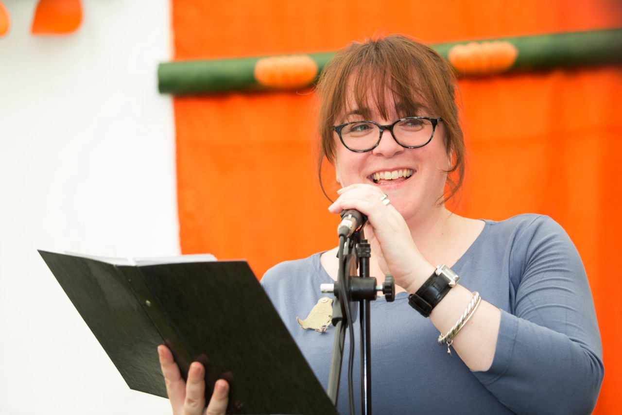 Julia Bird, a white woman with glasses, smiles on stage into a microphone and a folder of poems