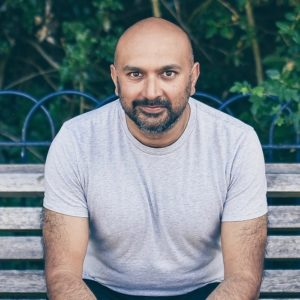 Photo of Bobby Nayyar sitting on a bench. He wears a white t-shirt and dark jeans.