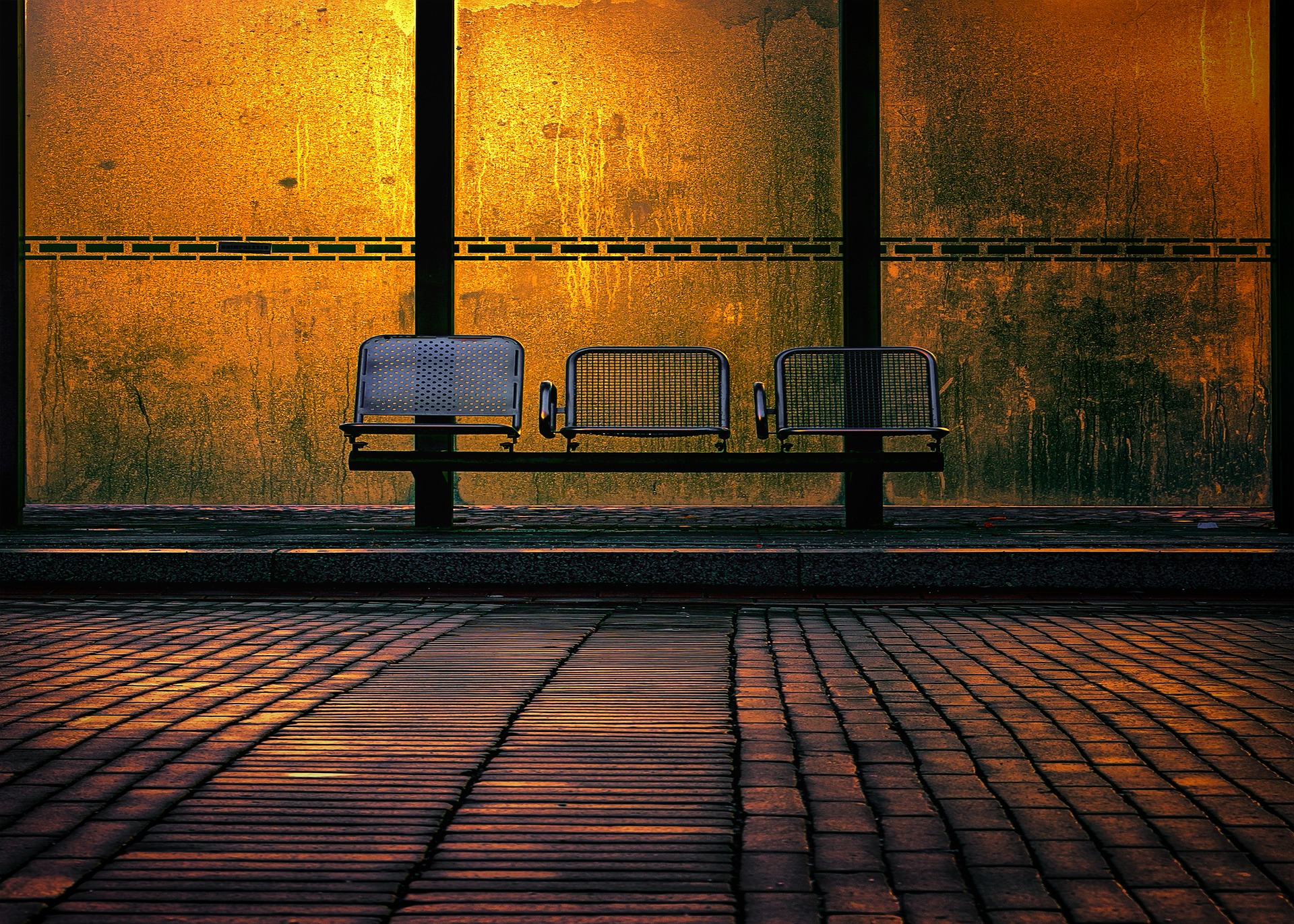 Image of empty seats at a bus stop at night, with a yellow light in the background
