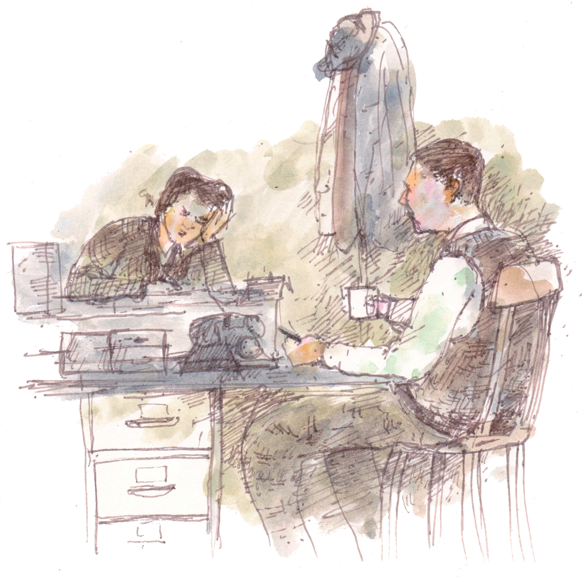 two people sit at a desk working through papers
