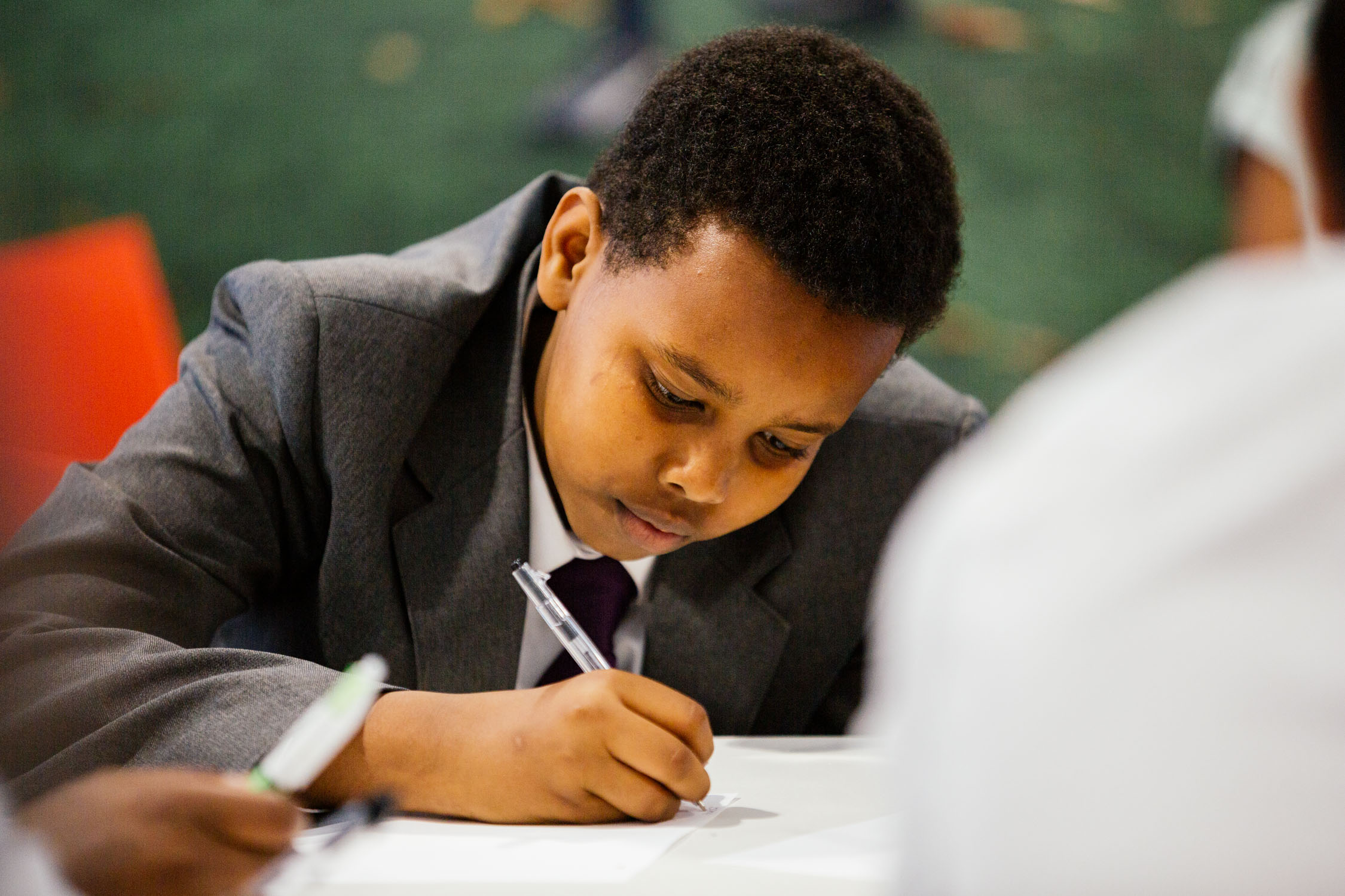 photo of young man concentrating on writing