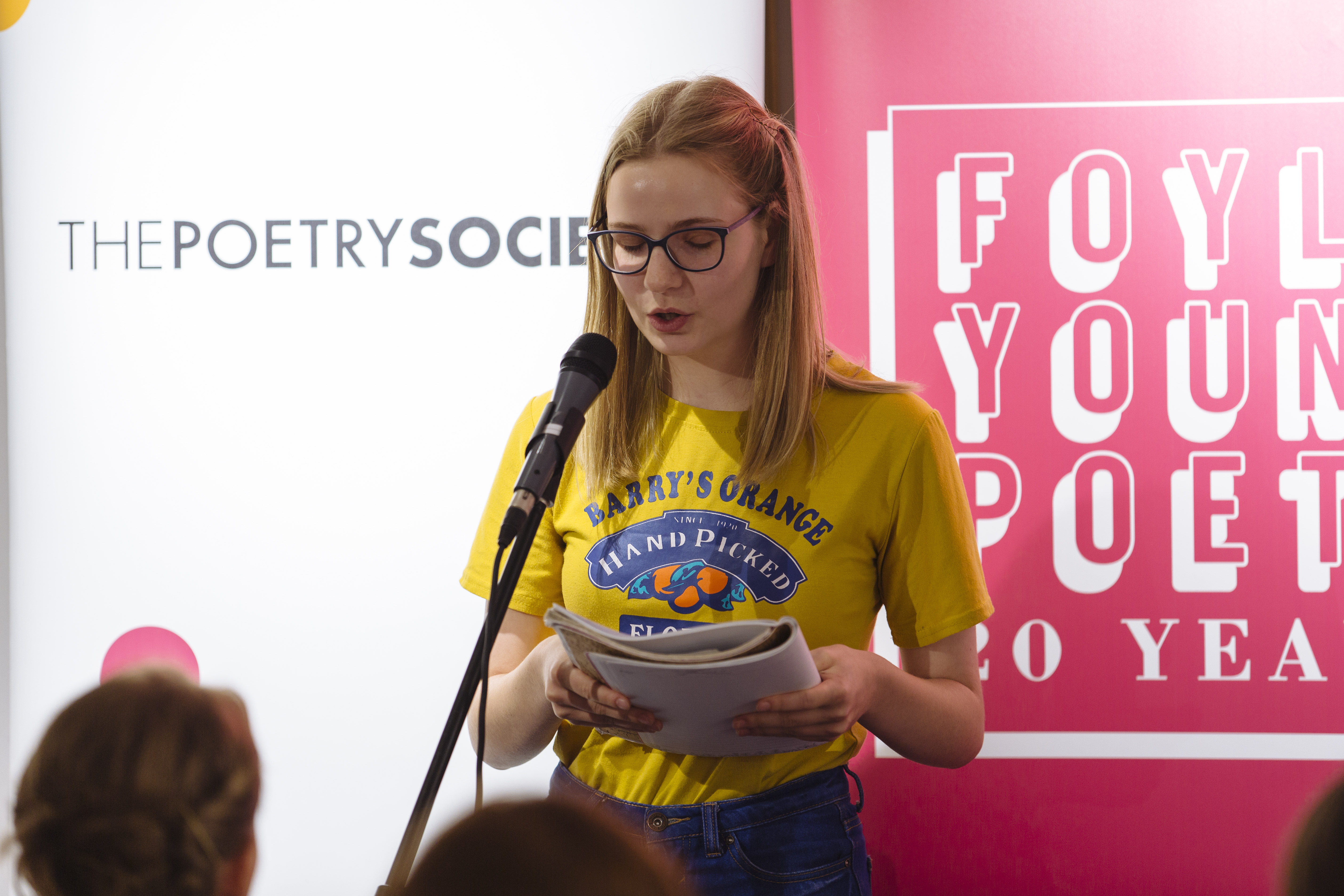 image of young woman reading in front of two Poetry Society and Foyle Young Poets banners