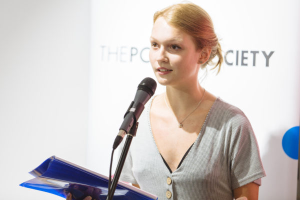 Photo of Nadia Lines reading at a microphone. She is a young white woman. Her brown hair is in a bun and she smiles.