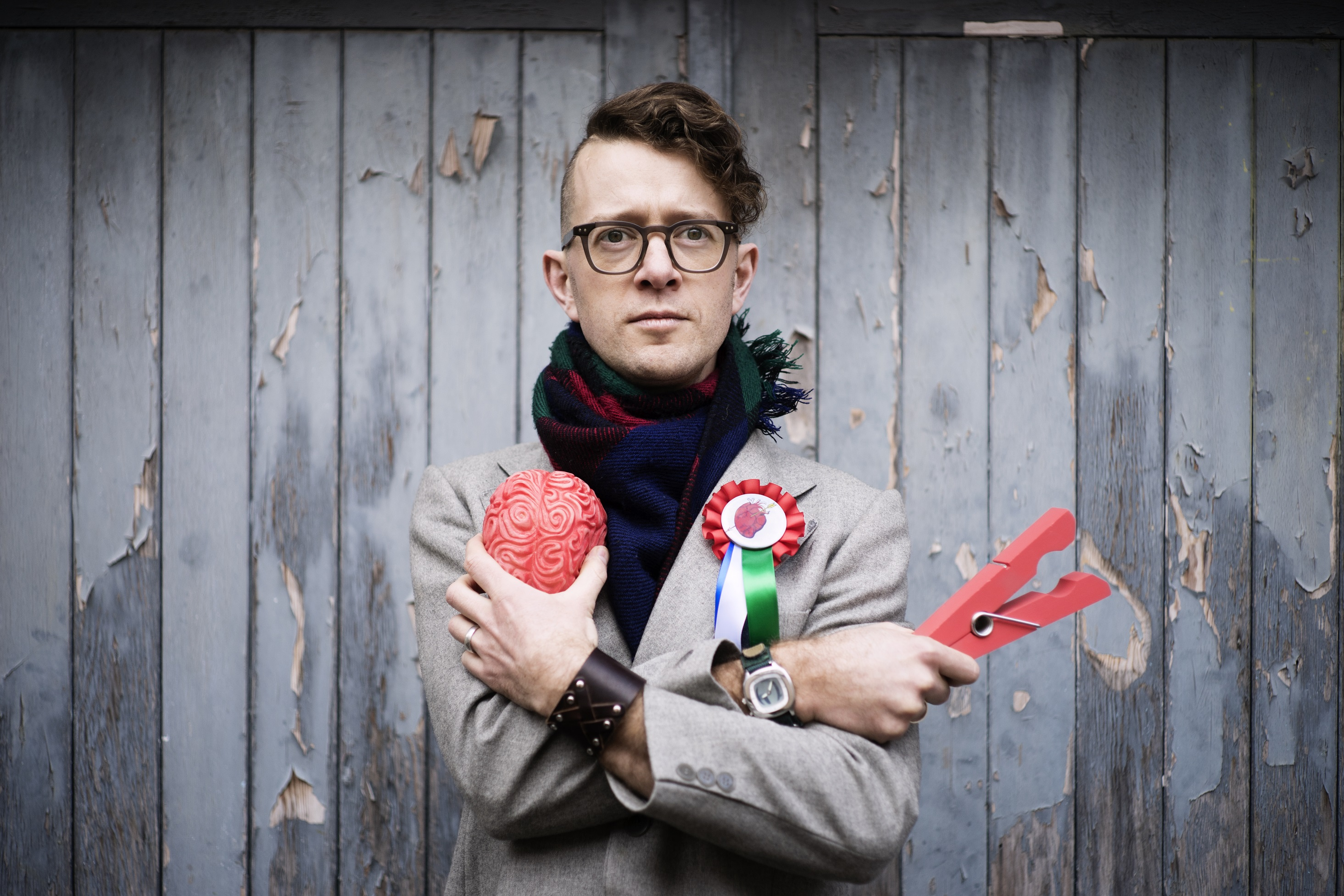 Caleb Parkin crosses his arms, holding a model of a brain in one hand and a giant coral-coloured clothes peg in the other