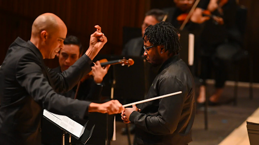 Photo of Yomi Sode speaking into a microphone in front of a conducter and Chineke! violins