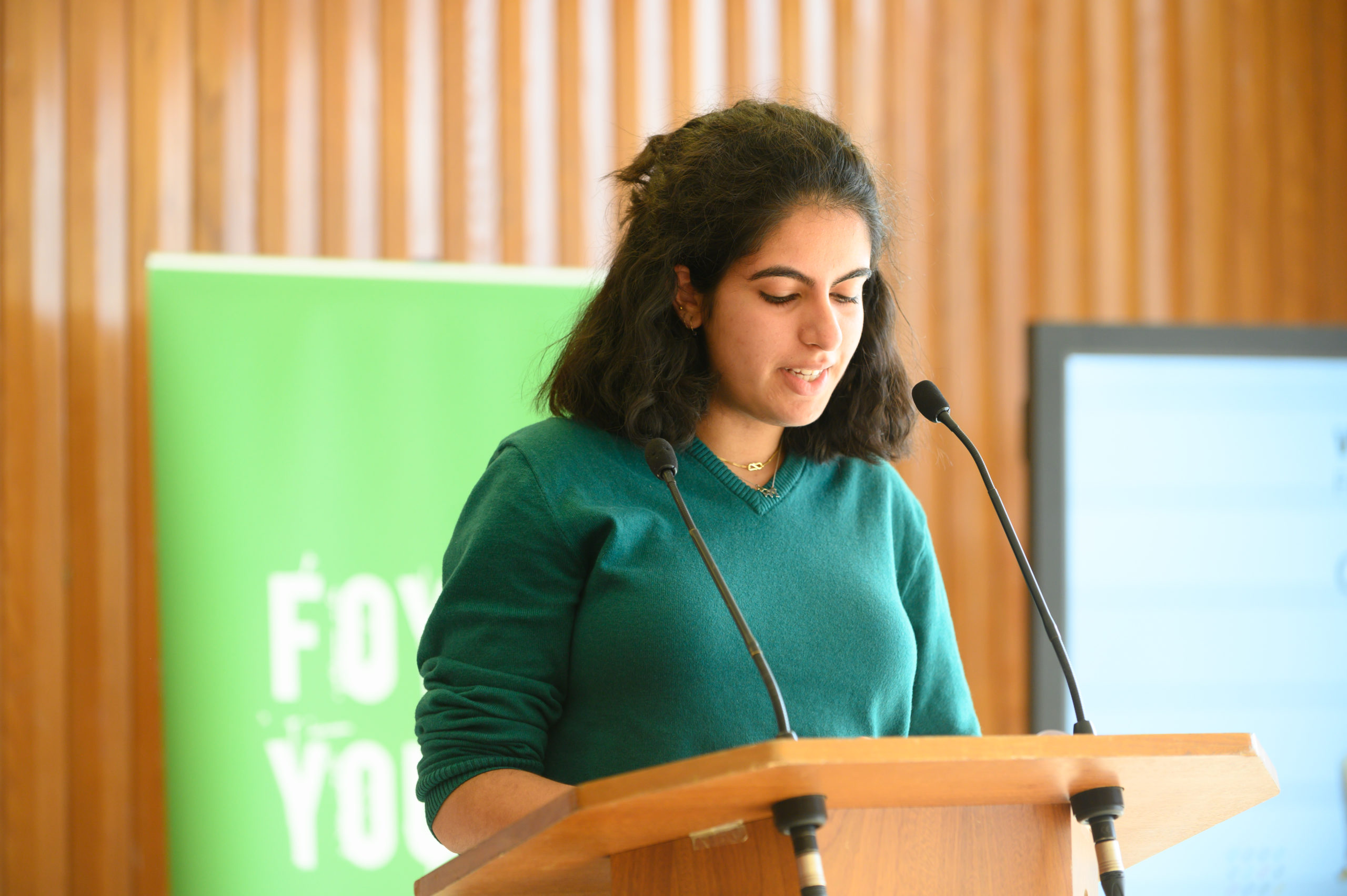 Photo of Cia Mangat reading at a podium with a green Foyle Young Poets banner behind her