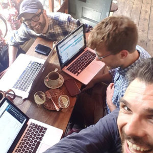 the three dog-ear team members crowd into a selfie with their laptops and coffee