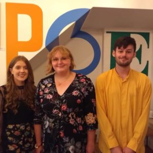 Lauren Aspery, Ellora Sutton and Jack Cooper standing in front of the POET mural in The Poetry Café