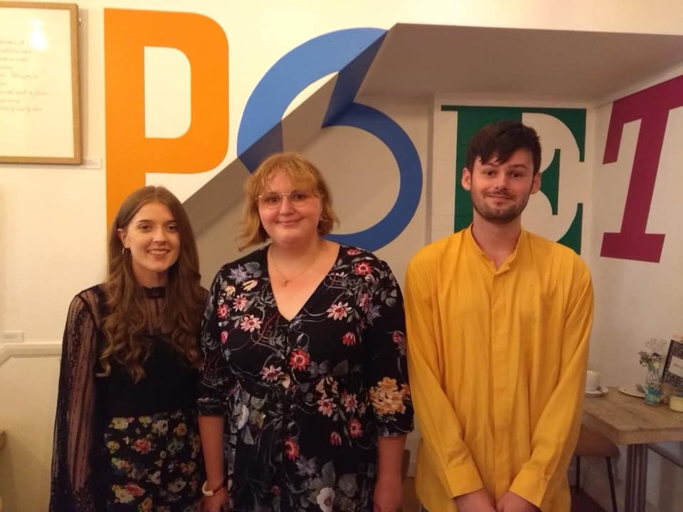 Lauren Aspery, Ellora Sutton and Jack Cooper at The Poetry Café for Art Does Not Get You A Job launch, standing in front of a POET mural