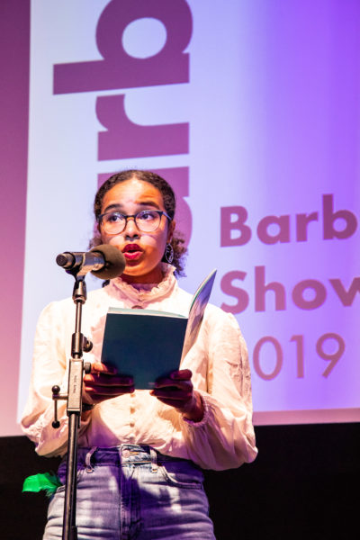 Photo of Esther Heller reading from a book on stage with 'Barbican Showcase 2019' in the background