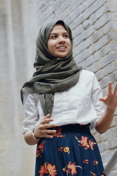 Fathima Zahra gesturing as she performs a poem