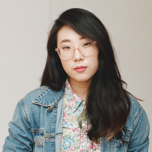 Photo of Franny Choi, a Korean American woman with long hair, wearing glasses, a denim jacket.