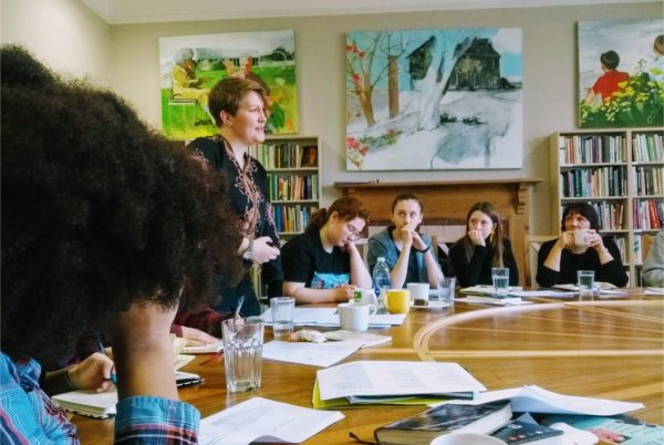 Caroline Bird stands at a table speaking to young writers
