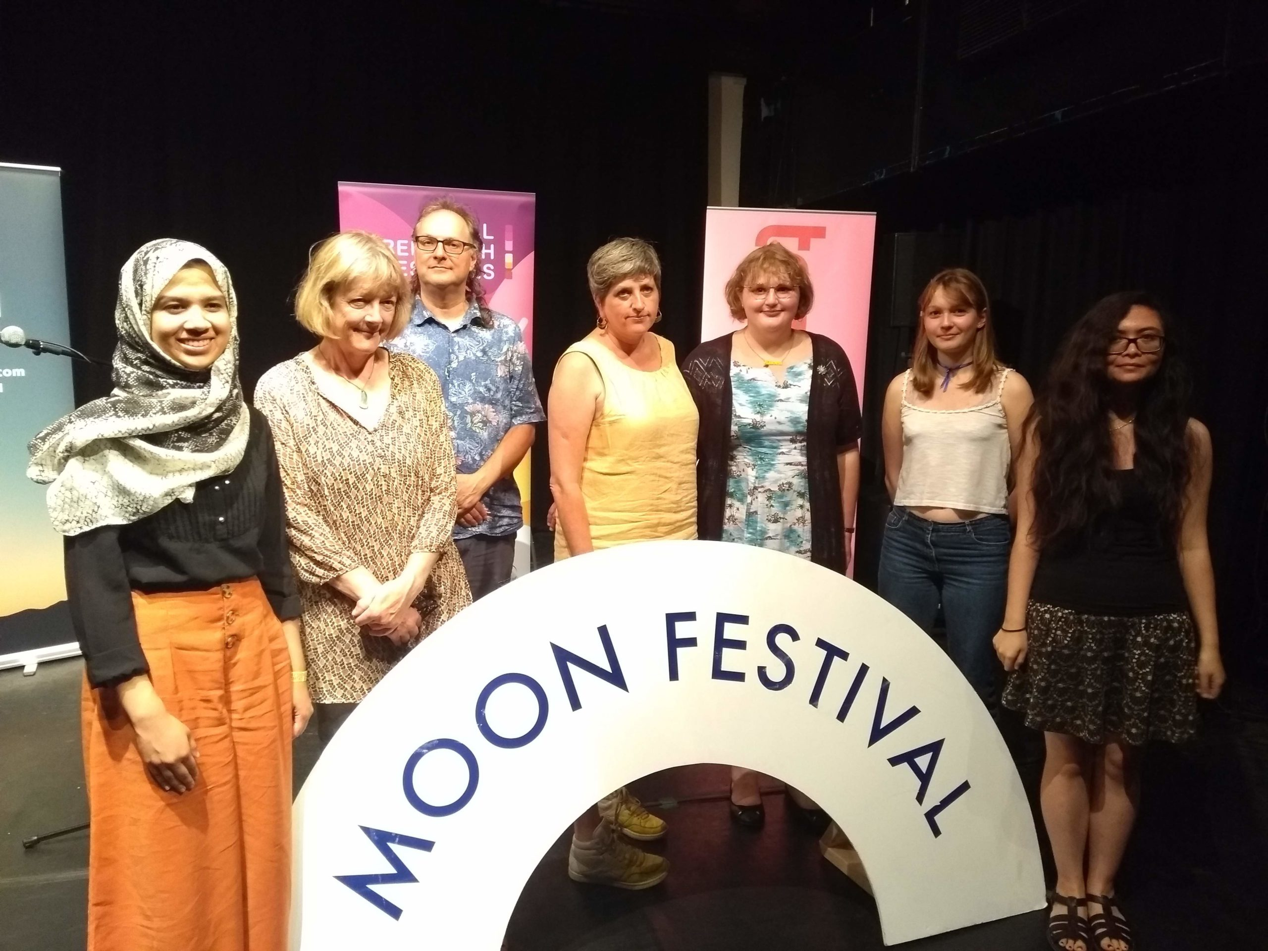 "Fathima Zahra standing with other young poets and Poetry Society members in front of a sign saying ""Moon Festival"""