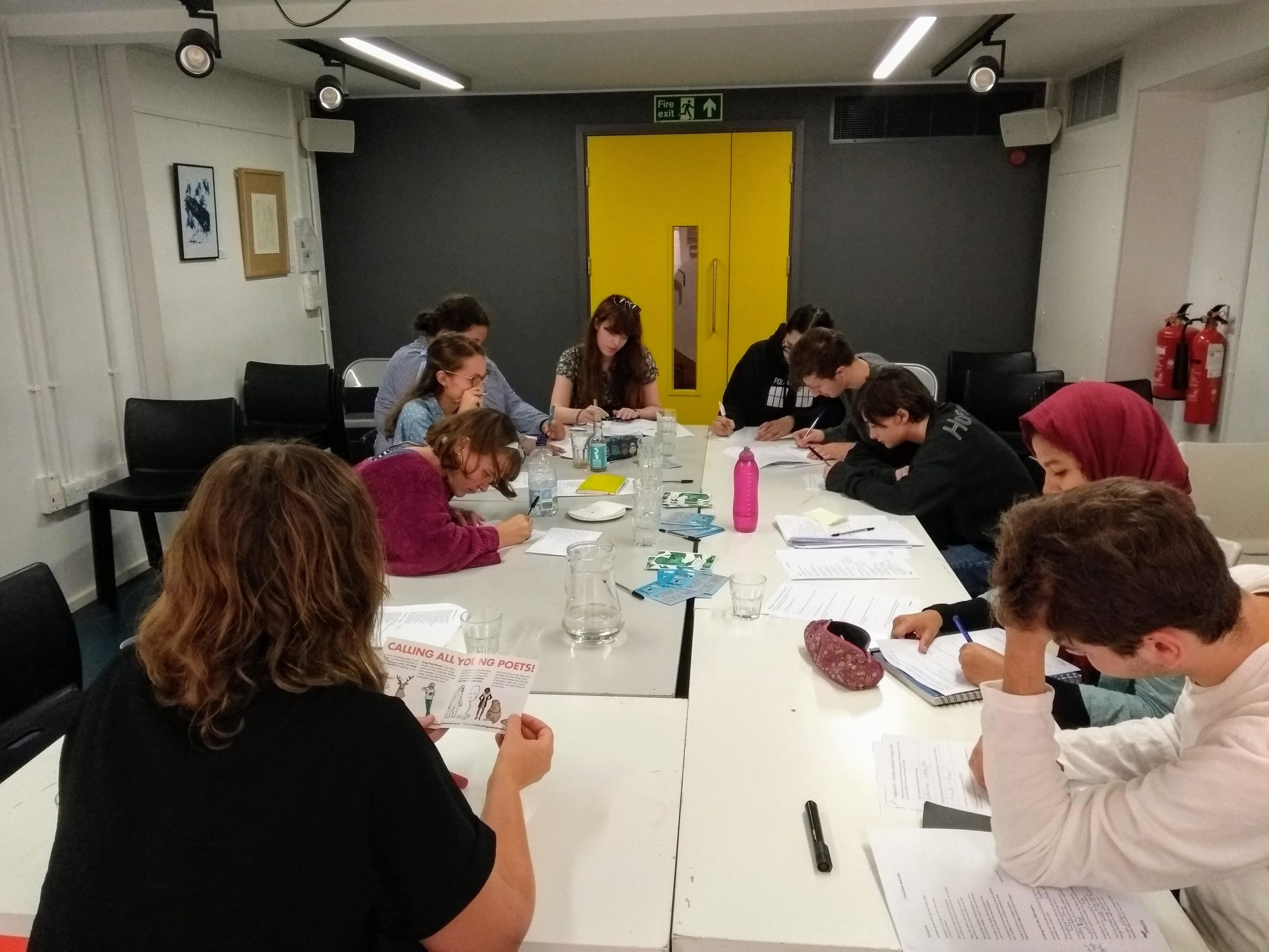 Clare Pollard leading the poetry translation workshop in the basement of The Poetry Café - the group is writing