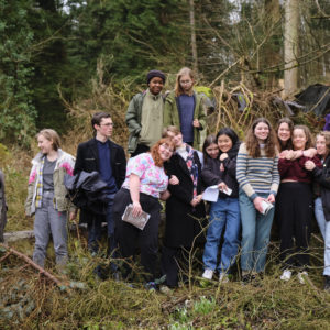 Photo of a group of fifteen Foyle Young Poets standing together in the woods hugging and grinning