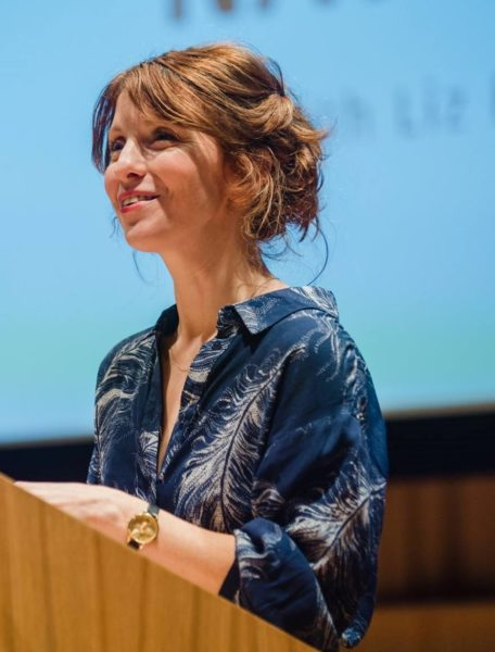Liz Berry stands at a lecture podium