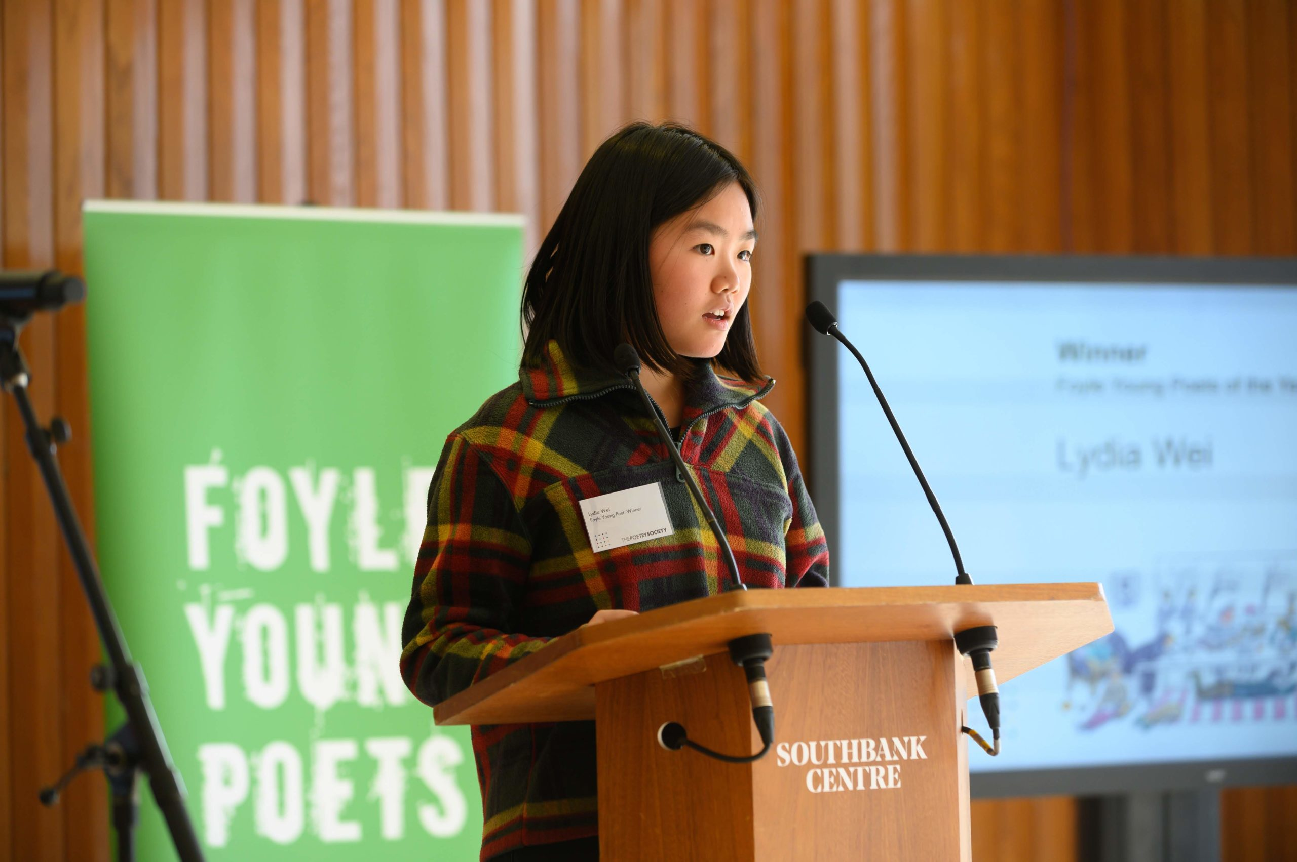Lydia Wei performing at a podium with Foyle Young Poets in the background