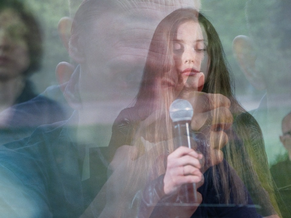 Several photos layered on top of one another: Maria holds a microphone with her eyes closed, and over the top of that Steven Fowler's face is imprinted ghost-like