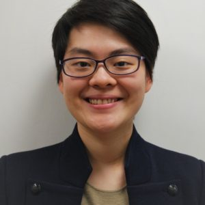 Image of Mary-Jean Chan smiling, wearing glasses and a black jacket