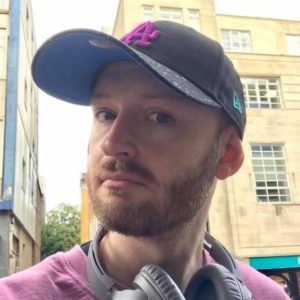 Photo of Matthew, wearing a blue baseball cap, headphones round his neck, a red-pink top and a beard