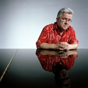 Ian McMillan in a red shirt leans over a table