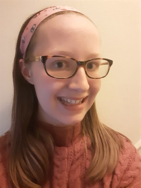Photo of Miriam Culy, a young white woman with glasses and straight shoulder-length brown hair, wearing a turtle-neck jumper and a pink headband