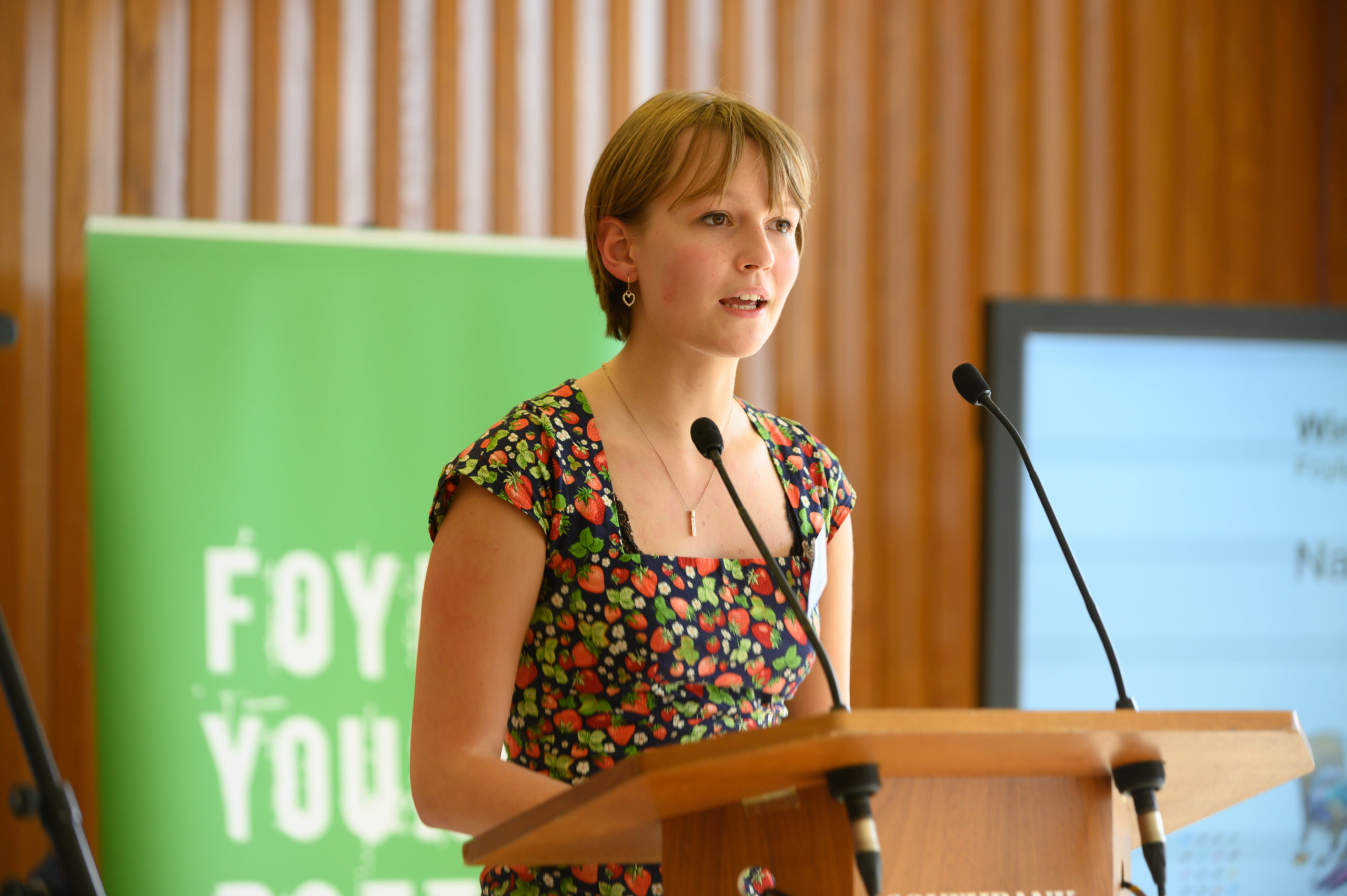 Photo of Nadia Lines reading at a podium at the Southbank Centre in front of a green Foyle Young Poets banner