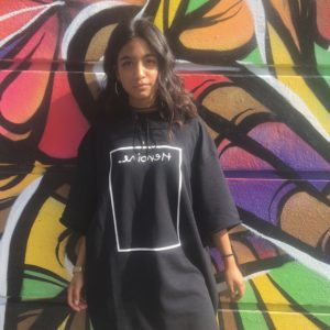 Image of Neha Singh, standing in a black dress against a colourful graffitied wall