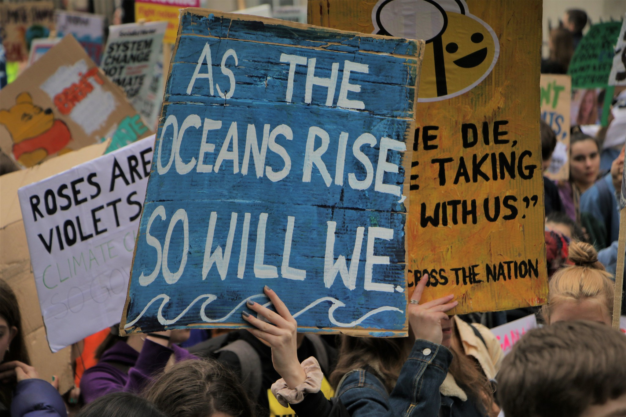 Photo of young people holding up signs. In the middle a blue sign says 'As the oceans rise, so will we.'