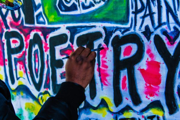 """A brightly colored wall with the word """"Poetry"""" graffitied in large, black letters in the middle, each letter surrounded by white paint. A person's hand is visible as they are painting."""