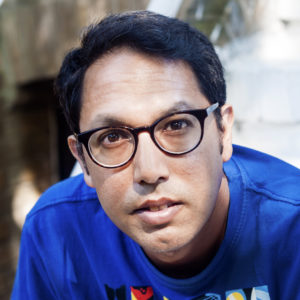 image of Rishi Dastidar wearing glasses in blue shirt