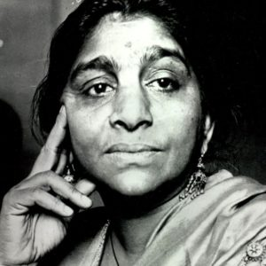 Black and white photo of a young Sarojini Naidu. She looks to one side with her hand to her face, wearing a sari.