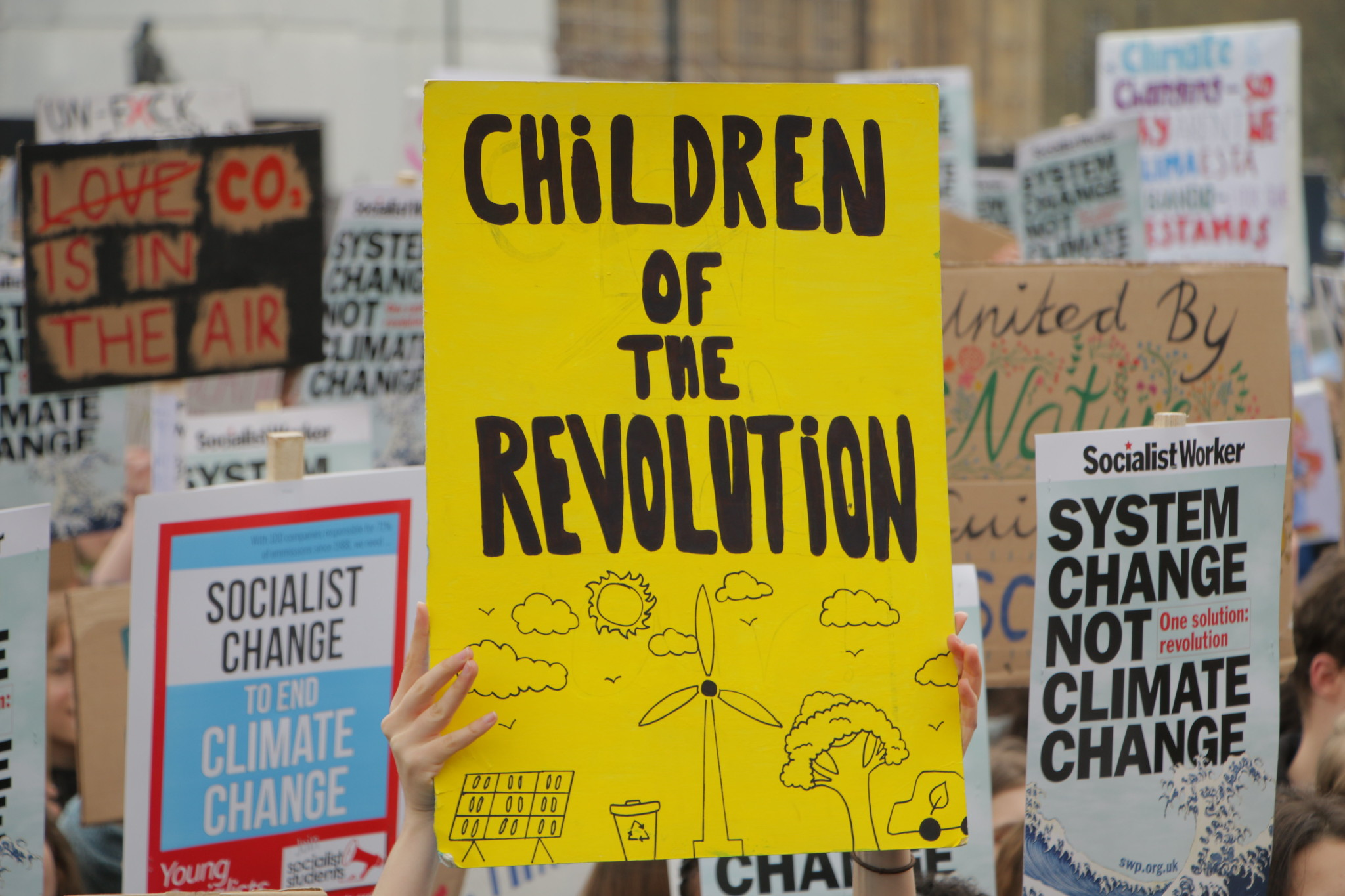 Photo of lots of different climate protest signs - in the centre a yellow sign says 'Children of the revolution' and is illustrated by wind farms