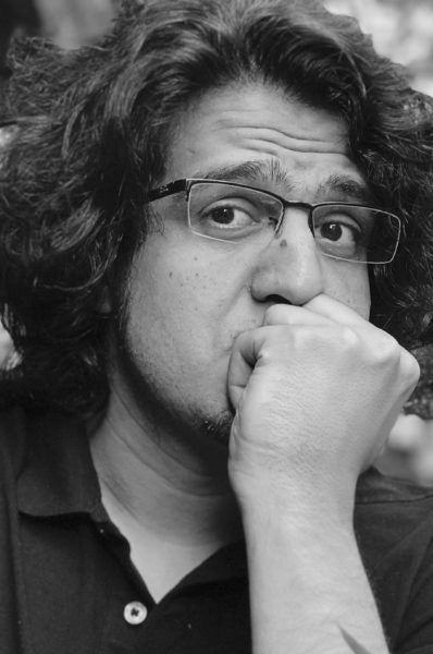 Photo of Suhrab Sirat: he rests his fist against his mouth and looks at the camera through glasses